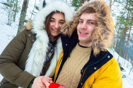 Funny young people. Winter holidays. The guy and the girl are smiling.
