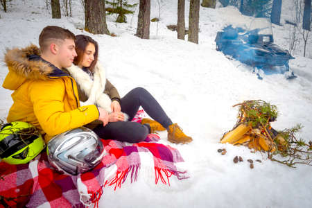 Snowmobile in the forest. The married couple has a rest in the winter at a fire. Bonfire on the snow. Traveling on a snowmobile. Lovers travel in the winter in the mountains.