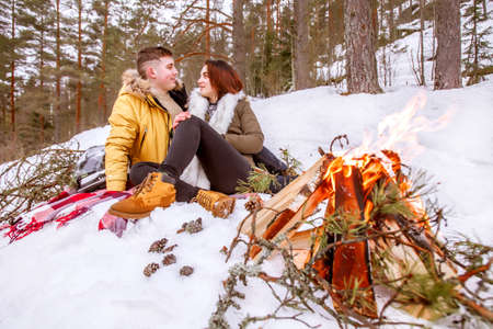 Lovers at the fire. Young people look at each other. Holidays in the mountains. Country holiday in winter. Bonfire on the snow. Picnic by the fire.