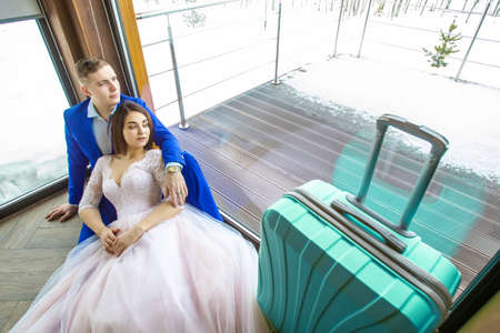 Wedding couple with a suitcase. Lovers think about honeymoon. Suitcase by the window. The bride and groom at the window. Journey in the winter.
