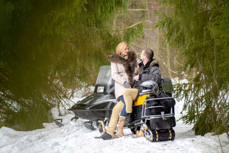 The couple rode a snowmobile. Winter fun. Married couple in the woods in winter. Journey in the winter. A man and a woman on a snowmobile. Archivio Fotografico