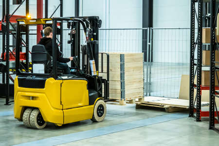 Warehouse equipment. Storage. The person works on a loader. Metal racks. Carton boxes. Forklift truck A man with a forklift loads wooden boxes.