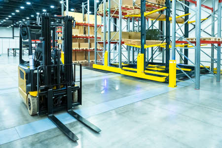 Forklift on the background of boxes. Stock. Loading goods. Cargo storage. Logistics. Forklift on the background of racks. Shelves in stock. Tiered metal shelving. Warehouse services.