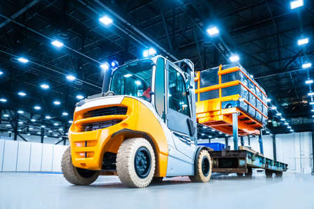 Diesel loader carries industrial lift with a load. Warehouse loader for transportation of containers. Loading oversized cargo. Transportation of industrial equipment. Special machinery. Banque d'images
