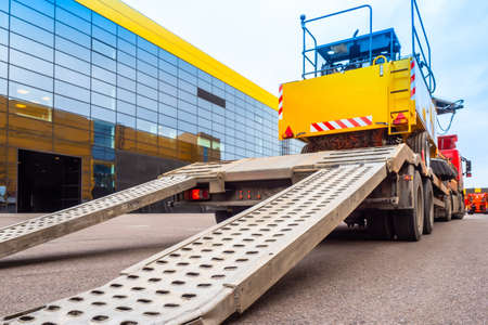 Trawl transport special machines. Loading of special equipment on the tow truck with the help of ladders. Aluminum ramps for vehicles. Trawl with aluminum ramps. Transportation of oversized cargo. Standard-Bild