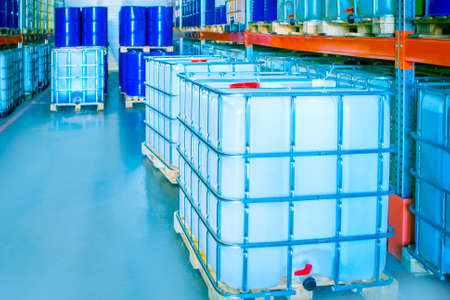 Chemical warehouse. Plastic containers for chemicals are placed on the shelves. Pallets with chemical containers. Warehouse equipment. Barrels are kept in stock. Warehouse storage. Logistics in stock.