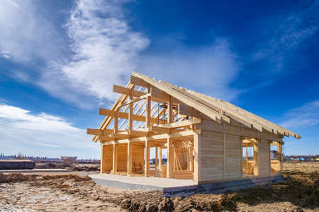 Frame of building house. Construction of the cottage timber. The wooden base of the house. Construction site sunlit. Building of private house. Banque d'images