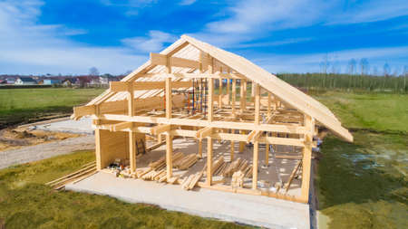 The frame of the house under construction. Building a cottage of timber. The wooden base of the house. Panorama of building a house on a building site.