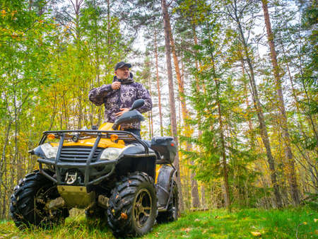 A man paves the route on the phone. ATV. A man rides through the forest on an all-terrain vehicle. Quad bike. Trip to the forest on ATV. The traveler checks the route on the map on the phone.