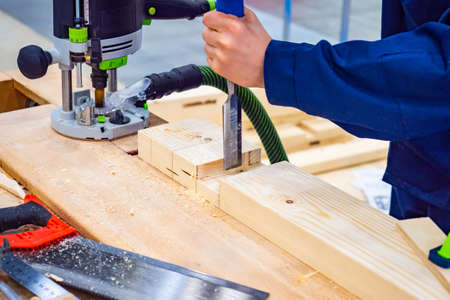 A man works with a wood chisel on manufacture. Milling machine for wood. Sanding machine for wood. Furniture manufacture. Woodwork.