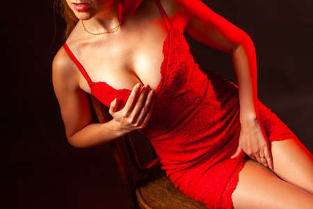 Sexuality. Excitation. Female figure. A woman touches her body. Woman in sexy red dress. Sexual fantasies.