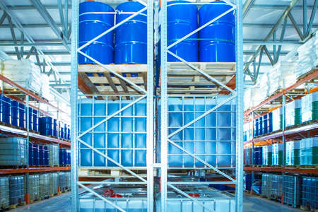 Warehouse storage. Barrels are on racks in stock. Containers for liquids stored in stock. Storage of chemicals in barrels. Plastic packaging for chemicals. Chemical industry.
