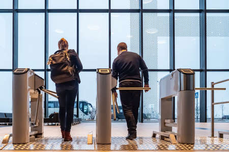 People pass through the checkpoint. Turnstile. Visiting control. Metal Turnstiles. A man and a woman go through the checkpoint.