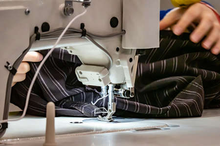 Clothing industry. Sewing machine. Atelier clothing. A woman works at the sewing machine. Tailoring. Training tailoring.