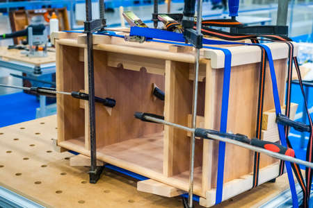 Carpenter work. Joiner's product. Tool. Furniture assembly. Pasting of wooden structures. Joiner's clamp. The product is clamped with clamps. Shop for the manufacture of furniture.