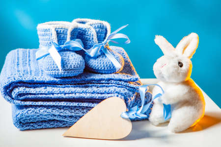 Pregnancy. The concept of waiting for the baby. Knitted baby shoes. Soft toy rabbit for the baby. Heart symbol. Clothes for the newborn. Newborn. Baby. Motherhood. Banque d'images