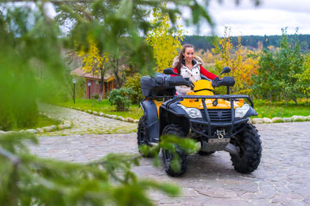 Girl rides on ATV. Travel through the nature of an SUV. The girl is pleased to walk through the woods. Entertainment in nature.