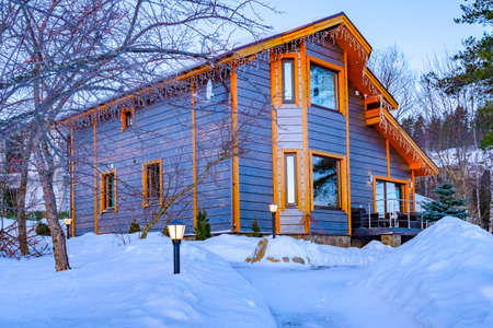 Winter two-storey cottage in Karelia. Houses in the snow. Christmas villa for family holidays. Recreation complex in winter. New year rest in Karelia. Houses for Christmas rent outside the city. Фото со стока