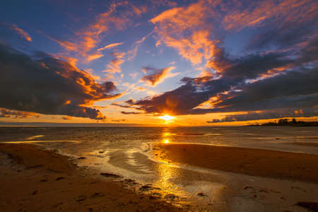 Sunset over the water. Orange sunset. Sunset at low tide. 免版税图像