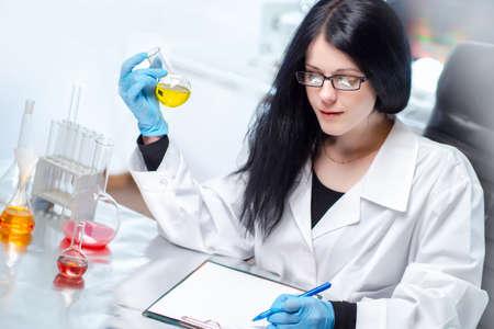 Pharmaceutical laboratory. Female bioengineer picks formula for a new medical drug.