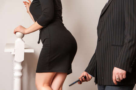 A man photographs a woman at work. Sexual harassment. A colleague photographs a woman without her consent. Banque d'images