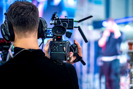 Video operator shoots on camera. Video camera with a transmitting device over Wi-Fi. Video production. Videographer in headphones. Video stream