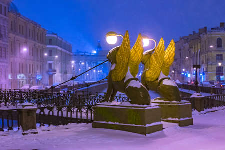 Saint Petersburg. Russia. Rivers Of St. Petersburg. Bridges Of St. Petersburg. Bank bridge. Griboedov Channel. Griffins with Golden wings. Lights in a snowy city. Travel to Russia.