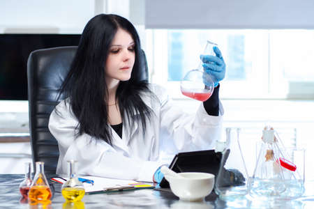 Pharmacy laboratory. A female pharmacist technologist mixes a liquid form of medication in a test tube. Manufacture of prescription drugs. Prescription department. Pharmacy production of medicines.