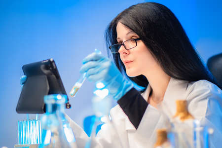 Pharmacy laboratory. The pharmacist looks in the tablet the required amount of the ordered medication. Manufacture of prescription drugs. Prescription department. Pharmacy production of medicines. Banco de Imagens