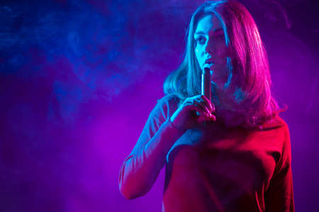 The girl holds the VAPE near her lips. The concept of vaping. A long-haired girl with a VAPE on a lilac background. Smoking an electronic cigarette. Place for the label.