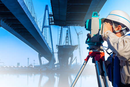 The surveyor works near the bridge. Geodesy. Geodetic measurements of roads and bridges. Theodolite or total station positioning against the city background. Geodesic equipment.