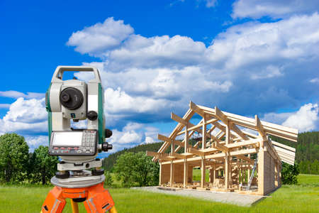 Surveyor on the background of suburban construction. Geodetic measurements in construction. Theodolite on a tripod is installed near the frame of the house. Geodetic equipment in construction. Reklamní fotografie
