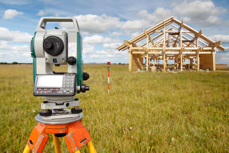 Geodetic works in construction. Surveyors install equipment on the construction site of the building. Theodolite or total positioning station at the frame of the cottage.