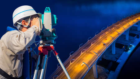 Surveyor on the background of the bridge in the evening. Geodetic works. Monitoring the condition of bridge structures. Measuring equipment.