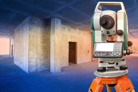 The surveyor works in a building under construction. Geodetic measurements. Construction equipment. Theodolite is installed in a house under construction.