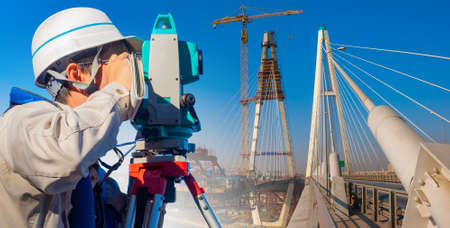 Surveyor on the construction of the bridge. Geodetic equipment in construction. Theodolite or full positioning station. Construction equipment.