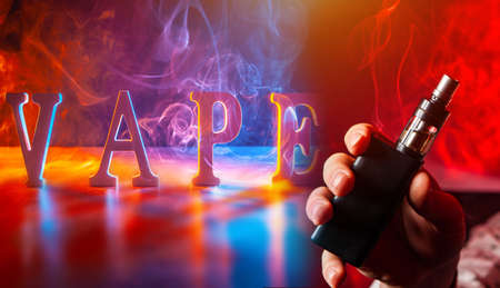 Vape Smoking. Three-dimensional VAPE letters and an electronic cigarette in the hand. Vaping on a bright background. Concept of electronic cigarettes. E-cigarette next to the VAPE text.