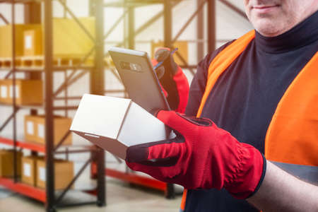 A man in work gloves on the background of the warehouse. The work of the storekeeper. A man with a smartphone and a cardboard box. Warehouse account. Warehouse activities.