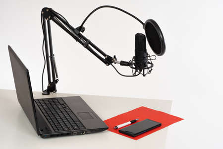 Desk with microphone and laptop in the recording Studio. The workplace is prepared for broadcasting. Microphone with pop filter and laptop on the desktop. Work with sound.