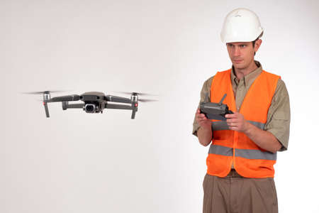 Geodesy using a drone. Surveyor in a white construction helmet. The surveyor launched the quadrocopter. A man watches the flight of a quadrocopter. The survey areas with the aid of drones. Imagens