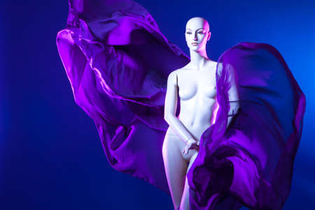 Fashion. Fashionable concept. Mannequin in silk. Purple fabric. Mannequin woman. Flying fabric.