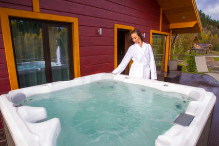 A white whirlpool bath is installed on the veranda of the cottage. Summer day. Beautiful woman near the hot tub with hydromassage. Spa treatments in hot tub. Relaxing in bubbles. Banque d'images