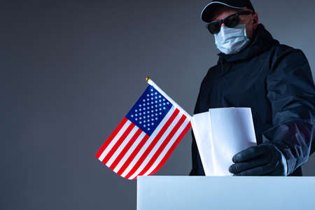 Violations in the US Presidential election. A man in black glasses and rubber gloves puts a stack of ballots in the ballot box. Election fraud. Illegal voting by an American in black clothing.
