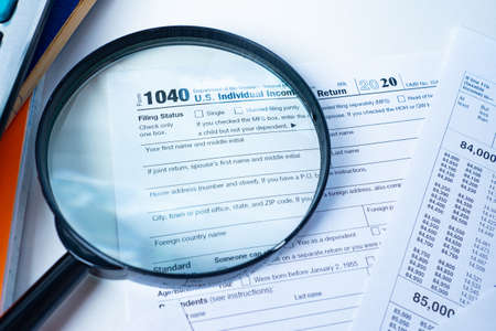 Form 1040. The Declaration for the individual income tax of the United States. American tax return form on the background of a magnifying glass. Tax payment control. Taxation of individuals in the US.