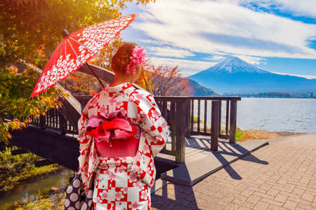 A Japanese woman stands at the bridge against the backdrop of mount Fuji and lake Kawaguchiko. A geisha with a red umbrella walks along the shore of the lake. Business card of Japan. Autumn in Japan.