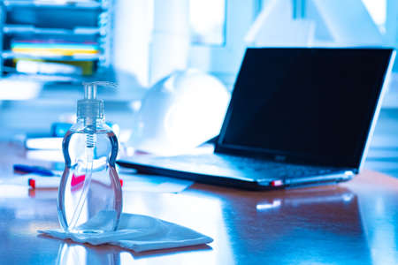 A bottle of sanitizer and a napkin next to the laptop in the office. Disinfection of office equipment. Sanitizers for cleaning. Sanitary treatment of premises. Preventing the spread of germs.