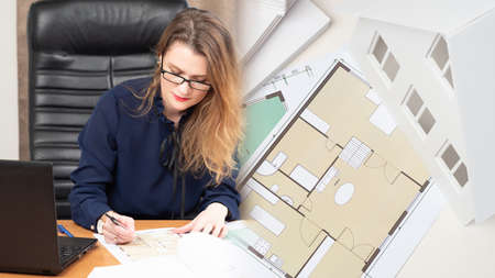 The architect is developing a project for a new house. The girl works in an architectural and construction Bureau. Preparation of a construction project based on the customer's wishes.