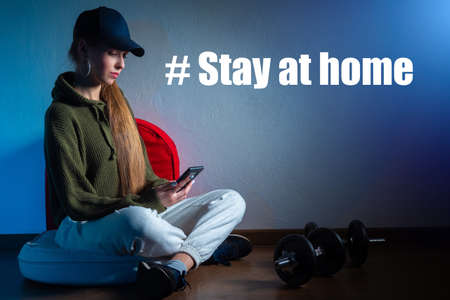 A girl in a tracksuit on the background of the inscription Stay at home. Measures of self-isolation during the epidemic. Quarantine for the coronavirus. Sports at home. Refusing to go to the gym.