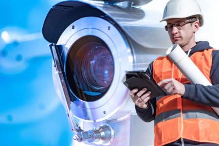 Engineer with a tablet on the background of a video camera. Video surveillance system project. Video surveillance throughout the territory.