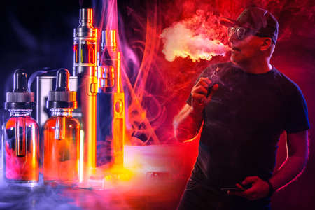 Smoking electronic cigarettes. VAPE shop. A man smokes a VAPE on a red and black background. A person with an e-cigarette and devices for Smoking. A man in the smoke from a VAPE.